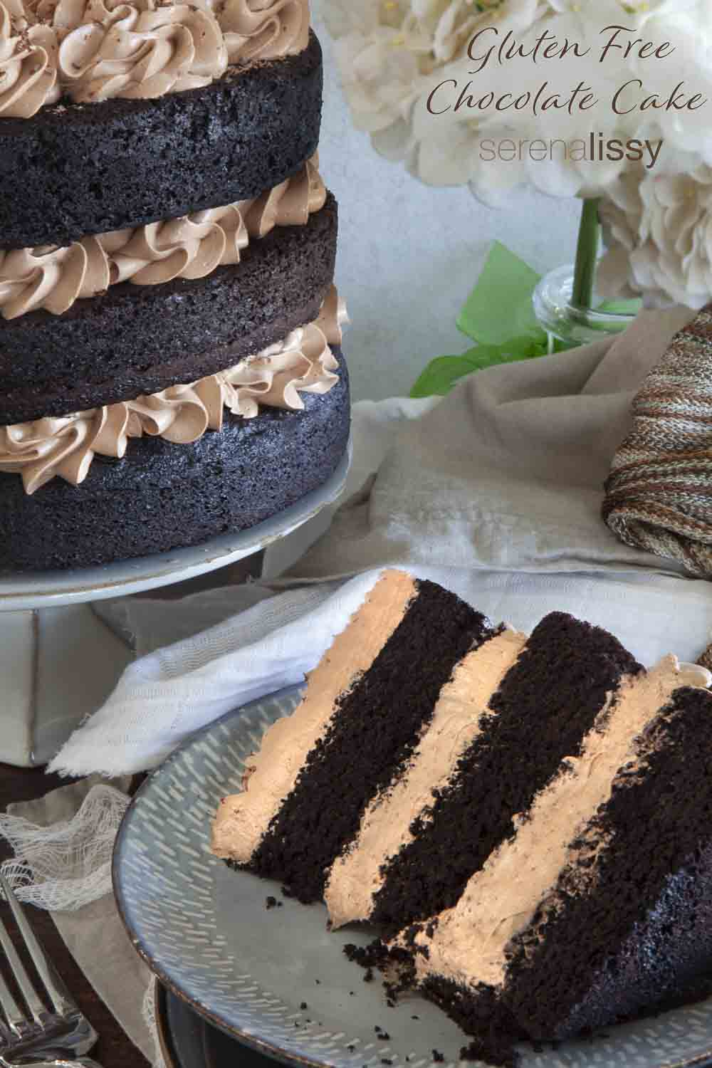 Slice of three layer cake next to the cake on a stand.